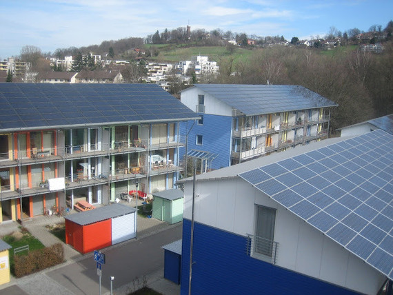 ソーラーシップの屋上から見たドイツ、フライブルグ市のヴォーバン地区にあるパッシブハウスと呼ばれる住宅。私の子どもは、子ども時代の4〜5年を写真の真ん中辺りに写っているミント色のアパートで過ごしました。住宅は4部屋あり、4階建てになっています。4部屋あるにも関わらず、この住宅にはバスルームに1つ、寝室に2つと、ドアが合わせて3つしかありません。そのため、屋根裏部屋はキッチンと3階下のリビングとなんの隔てもなくつながっており、3つ目の寝室として使うには問題があります(閉めるドアがありませんからね)。この構造を設計した建築家は、パッシブハウスでは建物全体の空気の流れを確保することが重要と考え、住人がドアを閉めることで空気の流れを妨げられるのを嫌がったのでしょう。しかし、他の建築家が建てた近所のパッシブハウスは、このような住人に不便を強いる設計にはなっておらず、実際そちらのほうがよく売れています。(クレイグ・モリス)